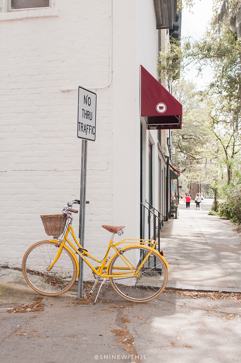 vintage yellow bike/bicycle with basket parked at coffee shop savannah