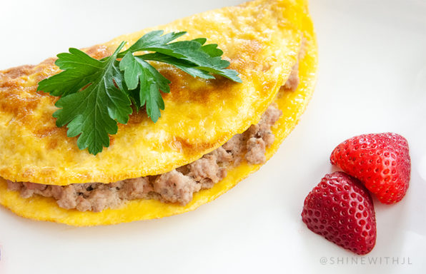 sausage omelet with strawberries on white plate