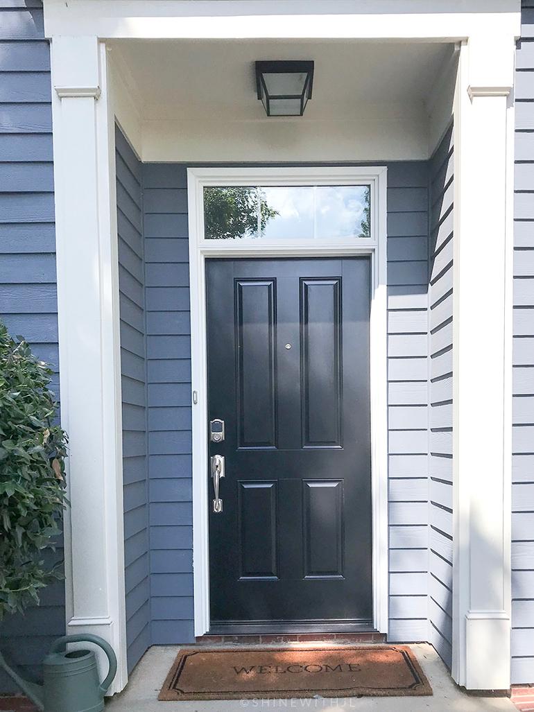 black outdoor light fixture black front door blue siding