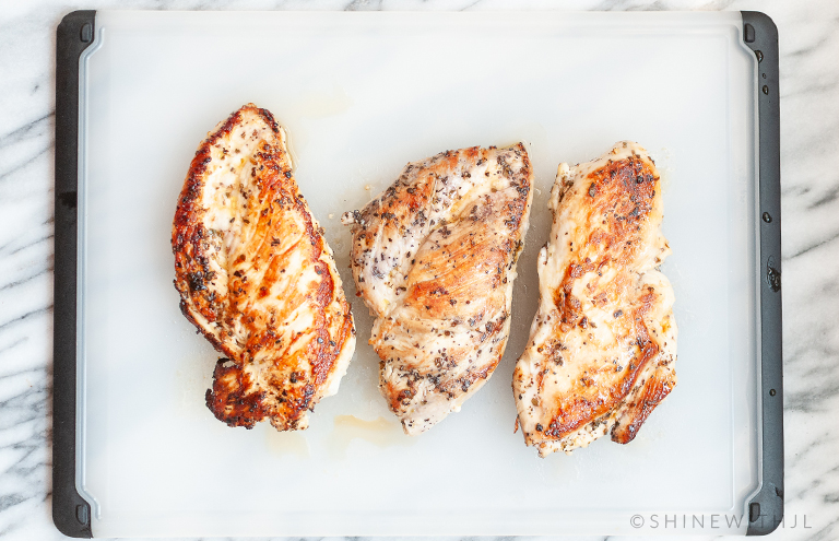pan cooked chicken breasts cooling on cutting board