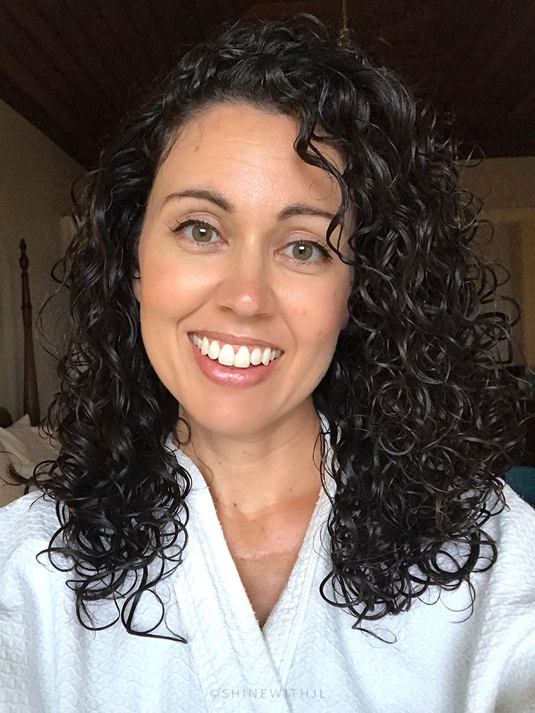 Curly haired woman in Sandals Resort bathrobe