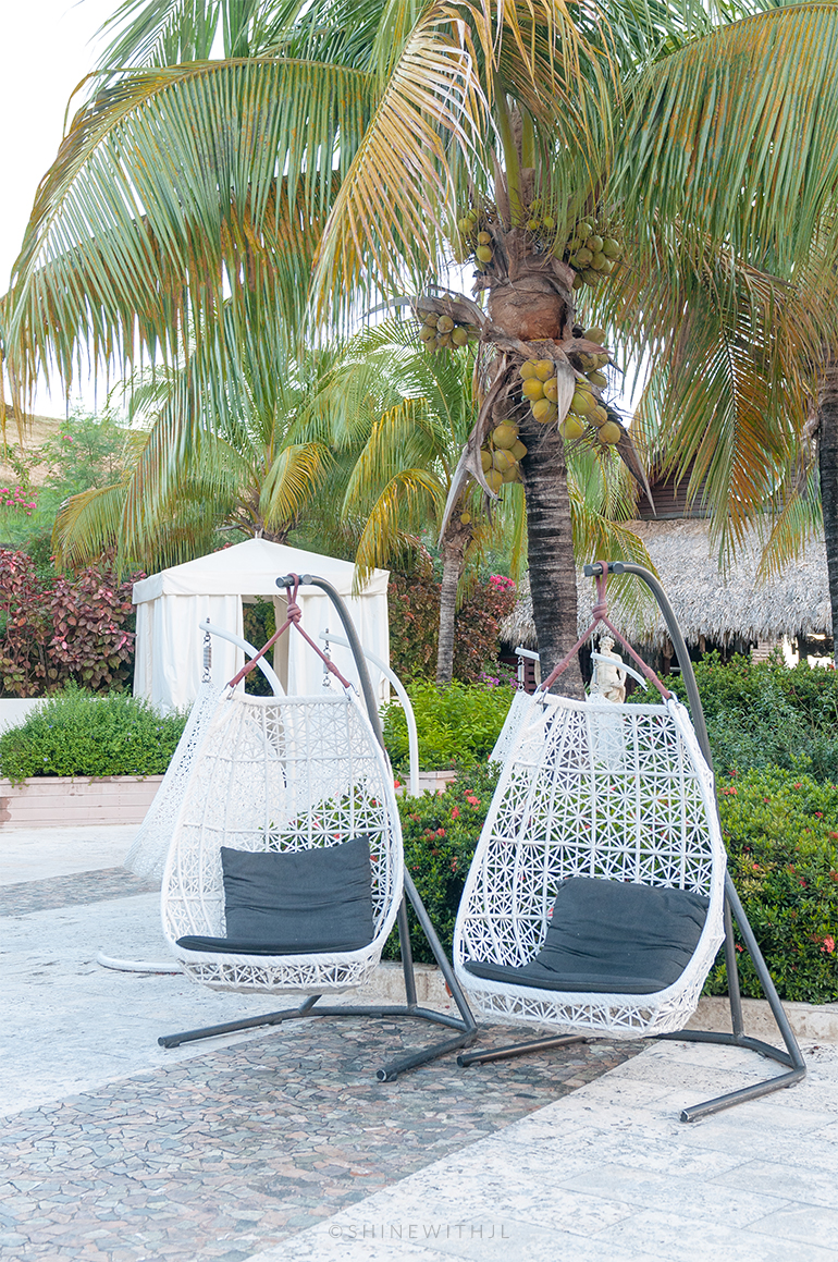 white wicker hanging chair with pillow sandals grenada