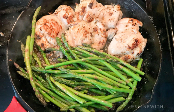 asparagus and herb chicken thighs in iron skillet