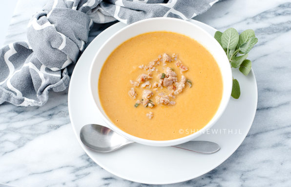 butternut squash soup in white bowl with sage
