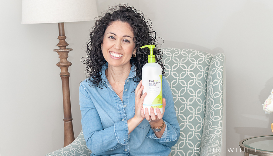 curly haired woman holding DevaCurl product on chair