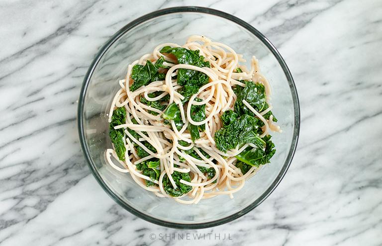 garlic parmesan kale gluten free pasta in glass bowl